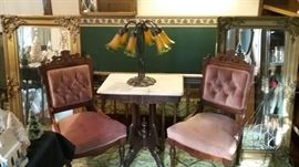 Two Eastlake chairs in front of beveled mirrors with golden frames.