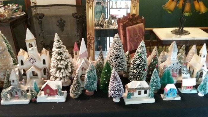 An assortment of Putz churches and houses accompanied by vintage bottle brush trees.
