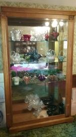 Beautiful curio cabinet containing vintage Fenton glass baskets and other glassware.