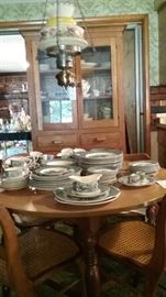 Currier and Ives dinnerware.  Oak hutch and caned oak chairs.