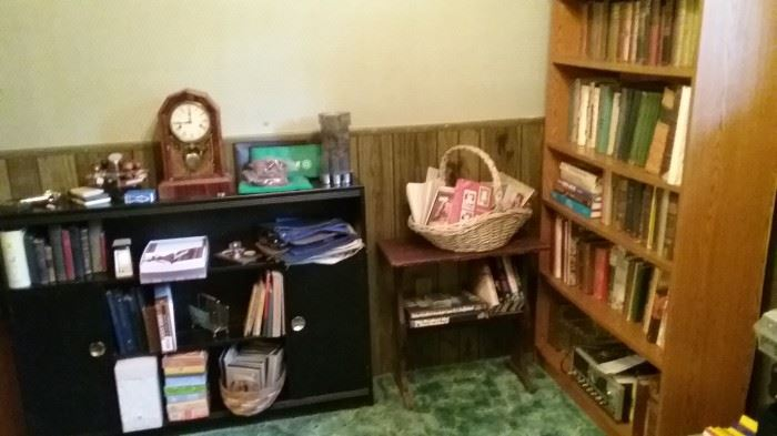 Variety of old books.  Many military topics.  Roughly 50 vintage Boy Scout and Scout Master manuals.  5-shelf bookshelf.  Low black bookshelf with two doors.  Vintage bank deposit bags.