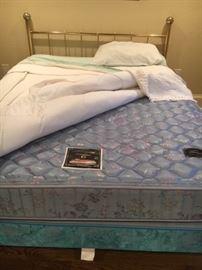 Queen mattress with brass headboard.