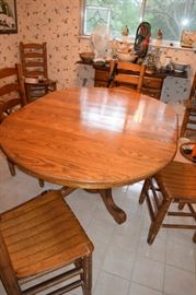 """Solid Oak Pedestal Table 36"""" Round Plus (2) 10"""" Leaves for 56"""" Oval Overall. 6 Oak Ladder Back Chairs"""
