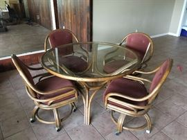 Glass top game table with four rolling chairs