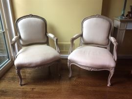 A pair of Louis XV style bergeres upholstered in beige linen