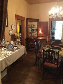 """The left hand side of the dining room has a table full of vintage glass and wonderful china including Lenox """"Hamilton""""  The Majolica is in the great antique corner cupboard and the Quimper is on a Victorian bamboo shelf"""
