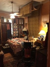 This is the Master Bedroom.  The hanging tapestry with rods and tassels with two matching cushions is for sale and is a wonderful statement to your bedroom.  Vintage quilts, a Victorian child's stroller with canopy, old trunks