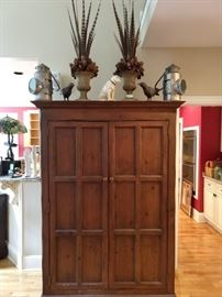 Nicer, vintage wooden storage armoire/Linen press, with  just-in-time for Thanksgiving pheasant feather urn doo dads, pair of metal blackbirds, pair of vintage galvanized tin railroad lanterns and a happy cast iron Nipper dog.