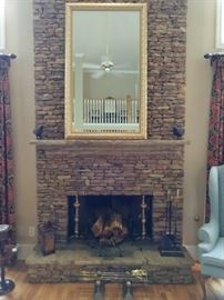 Soaring stone fireplace with large beveled mirror, antique English Brass andirons, antique English brass fire tools, contemporary fire tools and a small stack of wood, just in case.