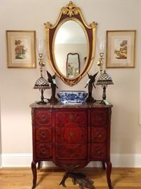 """Early 20th century mahogany, fruitwood and marble commode in the Louis XV taste, having a shaped marble top above a conforming case with gilt mounts and three drawers, the drawers decorated with a floral marquetry cartouche surrounded by parquetry inlay panels, the whole rising on dainty cabriole legs ending in gilt sabots; measures 30.5"""" h x 27.5""""w x 15""""d. Pair of vintage stained glass 2-light lamps, English blue/white porcelain footbath, pair of cast iron angels, pair of vintage Baldwin brass wall sconces, snapping cast iron crocodile, to nip the feet of unsuspecting shoppers and small children, vintage 1948 Hagemann mahogany shield mirror, with feather flourishes."""