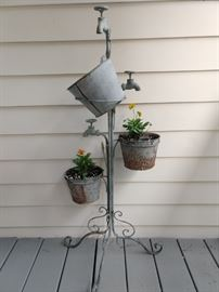A drippy galvanized steel planter, with orange violas, doing what they do best - bloom their heads off!