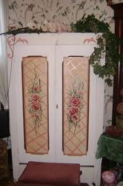 A PAINTED WHITE ARMOIRE THAT WAS CONVERTED INTO A TV CABINET WITH HAND PAINTED PINK FLOWERS