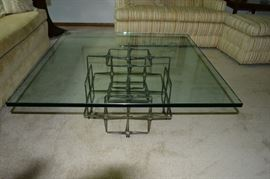 a thick sq glass top  on a steel nail base  a Paul Evans style