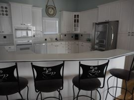 Crisp & clean white kitchen; stainless steel fridge with French doors