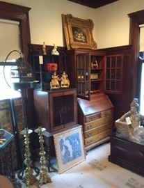 A view of the northwest corner of the dining room, showing massive antique brass candlesticks, a framed Thai or Cambodian print or rubbing, a pair of Chinese soapstone figures, a Japanese lacquerware tiered box, a vintage standing birdcage, a beautiful 2-part wood cabinet/desk ensemble, and so on.
