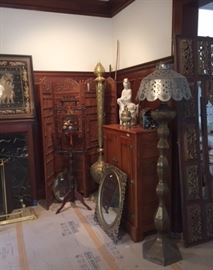 A view of the southeast corner of the dining room, showing a 4-panel carved wood floor screen, a bird cage hanging in a carved wood stand, a mirror framed in gilt wood, an antique ice box, and two tall, shapely Middle Eastern metalwork lamps.