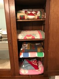 New and antique quilts, quilt tops, and hand-made afghans fill the selves of this East Lake Victorian Knock-down wardrobe.