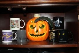 Six mugs, all from Broadway shows that came to Atlanta; Cats, Phanton of the Opera, City of Angels, Les Miserables, two more that I don't remember, plus a lighted pumpkin that is green inside.