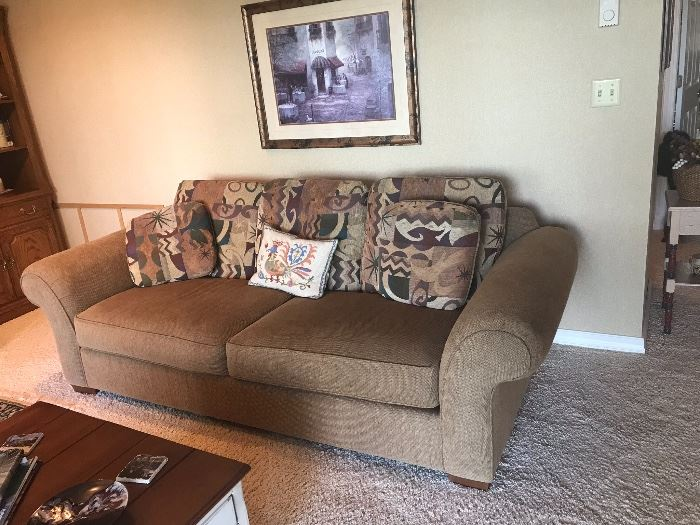 Loveseat in neutral tone with decorative pillows.