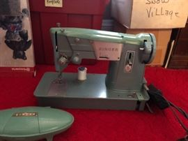 One of 2 vintage Singer sewing machines with attachments