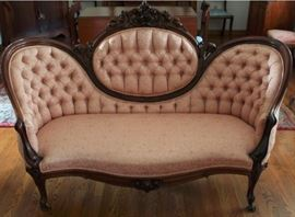 29 - SETTEE - Circa Mid 1800's, rosewood, finger molded frame with highly carved central crestail. cabriole legs, on casters, rose damask tufted upholstery.