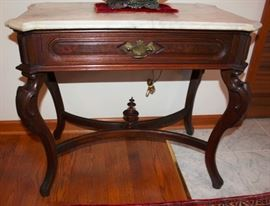1 SIDE TABLE  Circa 1860, walnut, canted marble top, sincle frieze drawer, cabriole legs, stretcher with urn shaped finial.