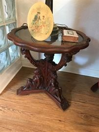 Antique Glass Top with Naked Women carved on the base supporting the table.  Price $ 50