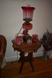 """Gorgeous and Rare Antique Aladdin Style Cranberry Oil Lamp featuring Cranberry Bowl and Cranberry Fluted Edged Lamp Shade notice also the Cranberry Fluted Edged Vase and the Fenton Glass Basket with Cranberry and Milk Glass """"Case Glass"""" with Handle. This all sets atop a Highly Carved Victorian Table with Scalloped Edging and Tear Drop Finials. Also is that a Cut Glass Pitcher I see on the floor to your right?"""