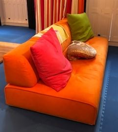 31) Pas Si Classique Armless Sofa from Ligne Roset Upholstered in Orange Ultrasuede. Two loose cushions, one in pink ultrasuede and one in acid green ultrasuede.