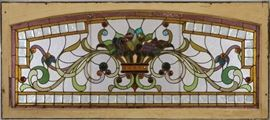 """A late 19th century Stained Glass Transom Window.  Multi color scroll, flower, and fruit design with cabochon and faceted glass accents in a painted wood frame.   Some cracked panels, one small piece of glass has been replaced.  64 1/2"""" x 28 1/4"""" high."""