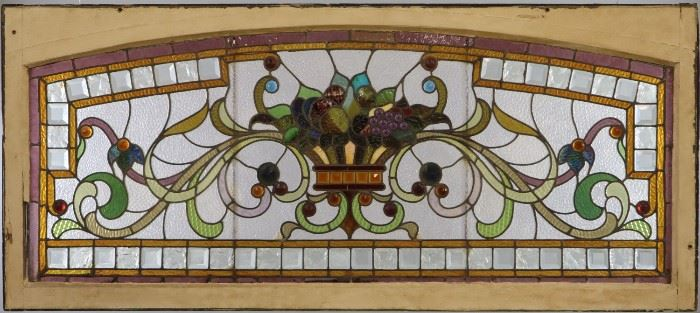 "A late 19th century Stained Glass Transom Window.  Multi color scroll, flower, and fruit design with cabochon and faceted glass accents in a painted wood frame.   Some cracked panels, one small piece of glass has been replaced.  64 1/2"" x 28 1/4"" high."