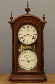 "A late 19th century American double dial shelf clock.  Southern Calendar Clock Co. ""Fashion No. 4"" model.   8-day spring driven time and strike movement with seconds bit and lower calendar mechanism, marked ""Seth Thomas Clock Co. ... Solely for the Southern Calendar Clock Co."".  Walnut case with single arched door.  Original finish with minor wear, original gilding on dial surround.  Running when cataloged.  32 1/2"" high overall."