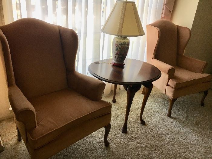 Pair peach color velvet Queen Anne chairs, round cherry drop-leaf table and Asian-theme lamp.
