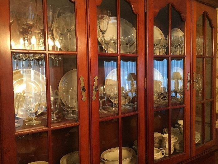 Beautiful cherry china cabinet filled with Homer Laughlin china and stemware.
