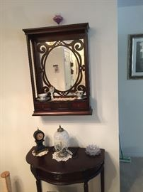 Mirrored wall cabinet with drawers, half circle table with Clock and small lamp