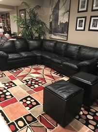 #100.       Black leather SECTIONAL  good condition.   $900.       Large geometric Rug $450.