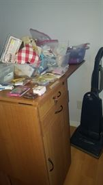 Fold Out Sewing Table on wheels.  Drawers & Cabinet on one side and Cabinet on the other.  Lots of sewing supplies.
