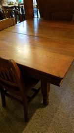 Antique farm table with 5 leaves. 150+ years old. Set of four very sturdy school chairs.