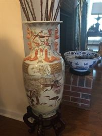 Orange and white Chinese porcelain vase with stand. 25 inches tall 10 inches in diameter