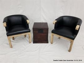 Barrel back club chair with black upholstery and carved arms. Mahogany-stained lift-top storage box.