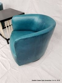 Teal barrel-back club chair. Square-top side table with turned spindle supports