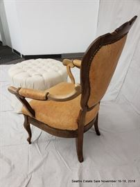 Shield-back leather upholstered armchair. Button-tufted white upholstered ottoman.