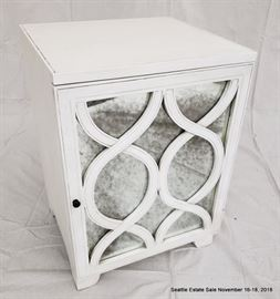 Mirrored-front single door cabinet with white finish.