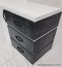 Black and white three drawer cerused wood dresser with leather handles.
