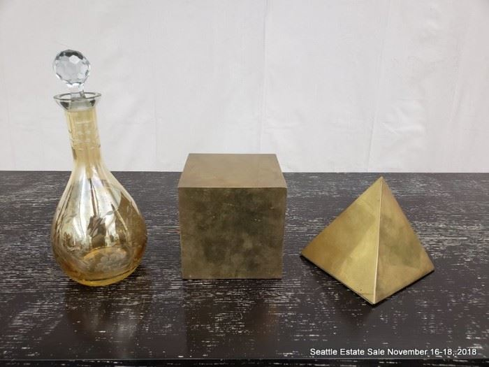 Gold-tone glass decanter and a pair of brass forms.