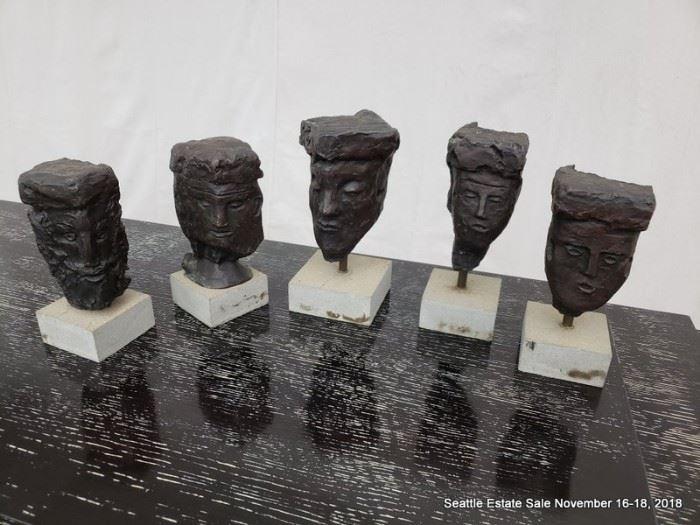 Suite of five primitive head sculptures on plinthes.