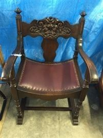 1930's walnut chair, carved man in the wind, custom upholstery in maroon leather and brass tacks. This is a conversation and show piece, in any room! VERY CONFORTABLE ON TOP OF ALL