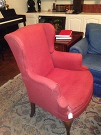 One of two red wing back chairs
