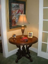 Living Room:  An oval Victorian table on casters is beneath another framed print.  Also shown is a gold tone lamp, brass clock (key will be with the cashier), decorative print and several antique books.