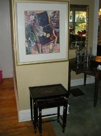 Living Room:  A framed print of a chair and flowers is above a set of two black lacquer nesting tables.